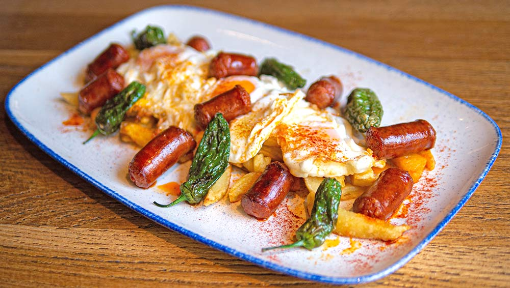 Soft yolk eggs sunny side uo with semi cured spanish sausage Restaurant Madrid